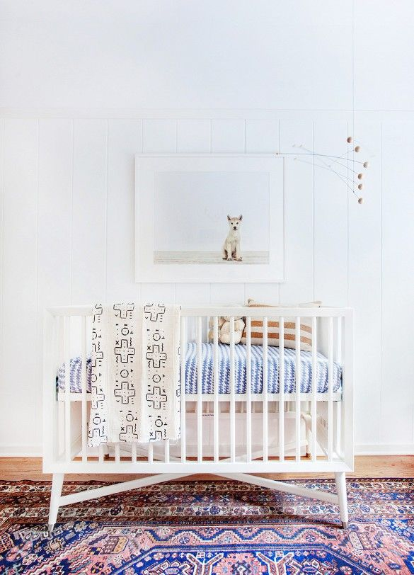 White wooden nursery crib with mixed textiles, wooden mobile, and baby animal photography art print.