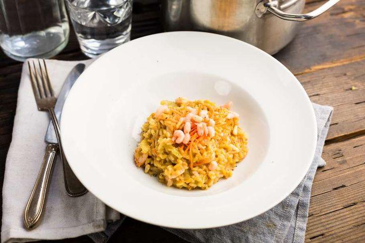 Recept voor romige risotto voor 4 personen. Met zout, water, olijfolie, peper, roze garnaal, roomkaas, kaas, droge witte wijn, ui, bleekselderij, groentebouillonblokje, wortel en risottorijst