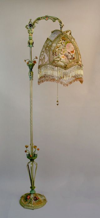 Ornate, intricately hand painted 1920s tole bridge lamp with dimensional flowers holds a Spring Garden shadwobox shade in soft, romantic pastel tones of pink, green, butter yellow, peach and lavender. Antique hand-dyed cut velvet and gold metallic lace overlay the panels and the shadowbox is filled with rare, heavy, luxurious 19th century French floral embroidery and Victorian era gossamer gold mesh.  Hand beaded fring, including vintage glass bugle beads, pick up all the colors of the…