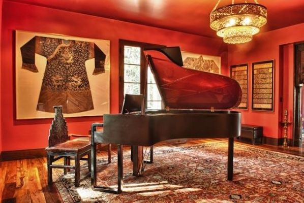 The centerpiece of the music room is a  Steinway grand piano designed by Karl Lagerfield. Qing Dynasty Chinese and Tibetan robes decorate one wall and a  Burmese lacquer bible is framed on the other. A Qing Dynasty chair from southern China sits next to the piano, atop a modern naturally dyed Indian carpet.