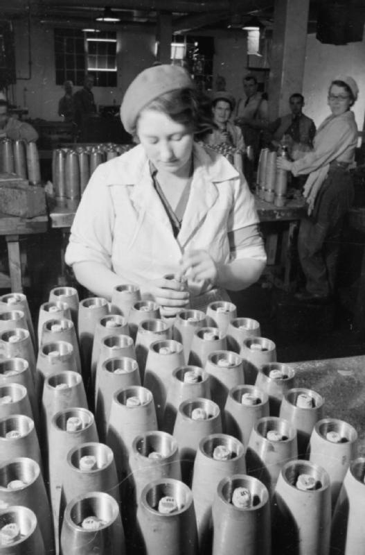 EVERYDAY LIFE AT A MINISTRY OF SUPPLY SHELL FILLING FACTORY, ENGLAND, UK, 1941. A female factory worker fits exploders into rows of shells at this filling factory. Behind her, other munitions workers can also be seen.