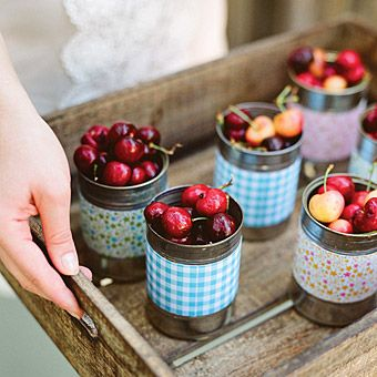 fresh cherries, presented in tin cans wrapped with decorative paper,