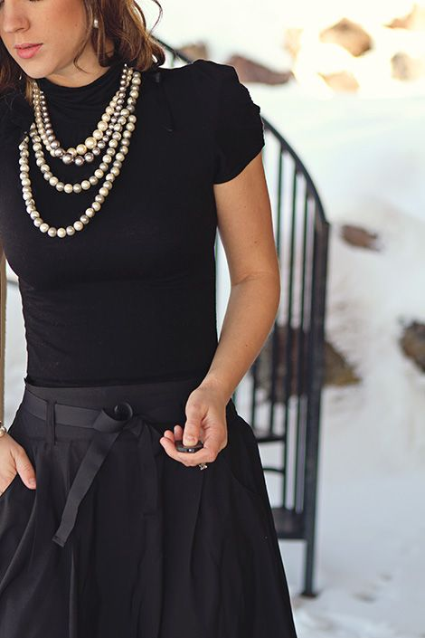 Black and pearls. knit and cotton combo. Soft puff sleeve knit blouse and rigid but feminine belted cotton skirt set nice with chunky pearls.