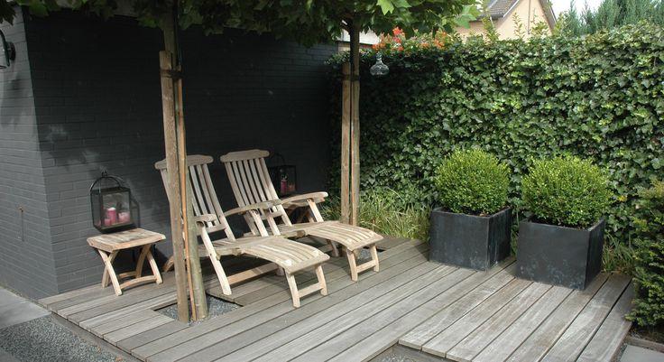 Rodenburg tuinen: moderne achtertuin met vlonder. Deze kleine achtertuin heeft elementen die de tuin toch bijzonder maken. De houten vlonder, het split en de oud hollandse tegels maken het tot een veelzijdige tuin.