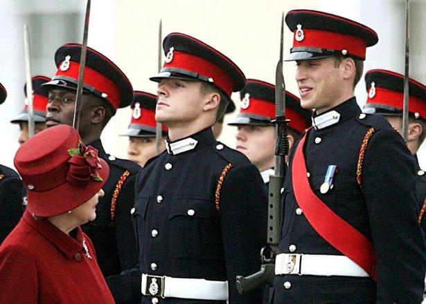 Queen Elizabeth II smiles at her grandson, Prince William, as she inspects graduates during a passing out parade at the Royal Military Academy Sandhurst in December 2006.