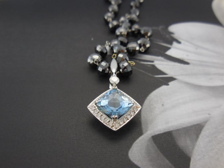 Handmade in 18ct White Gold, this enhancer showcases a stunning high quality cushion cut Aquamarine surrounded with small round diamonds and a diamond set enhancer. This is a detachable pendant which allows you to wear it with a chain, coloured gemstone strands, pearls or a neoprene cable.