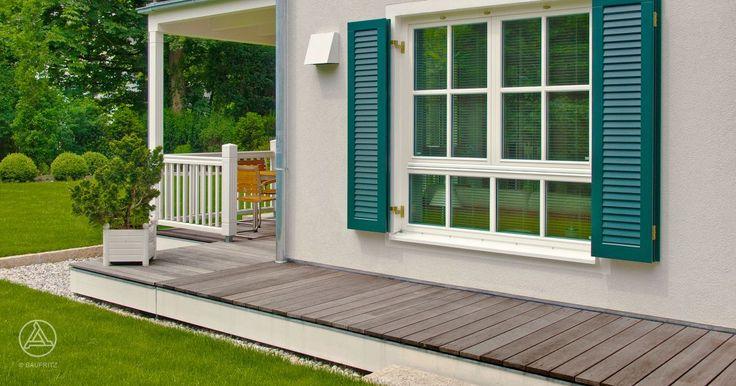 Die klassisch grünen Fensterläden beim Landhaus Steinhauser bilden einen Kontrast zur Putzfassade in dezentem grau – Baufritz