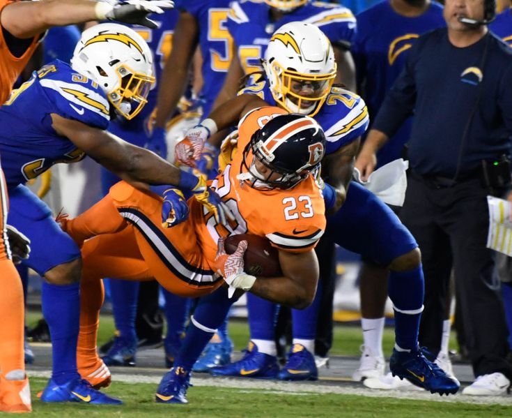 Broncos vs. Chargers:   October 13, 2016  -  21-13, Chargers   -      Denver Broncos running back Devontae Booker (23) pickup 17 yards after being brought down by San Diego Chargers free safety Adrian Phillips (31) and San Diego Chargers free safety Dwight Lowery (20) during the third quarter October 13, 2016 at Qualcomm Stadium. The Broncos lose to the Chargers 21-13.