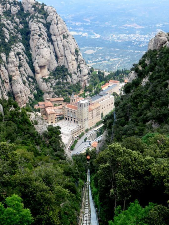 View of Benedictine monastery of Santa Maria de Montserrat - cable car or funicular up the mountain - great day trip from Barcelona - SoloTripsAndTips.com