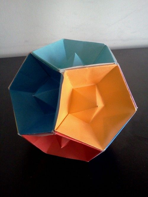 Modular origami. Dodecahedron with recessed faces, folded from 24 squares of 7cm kami. Design by Tomoko Fuse. Interestingly, though all 24 units are the same, they are joined in an asymmetric pattern.