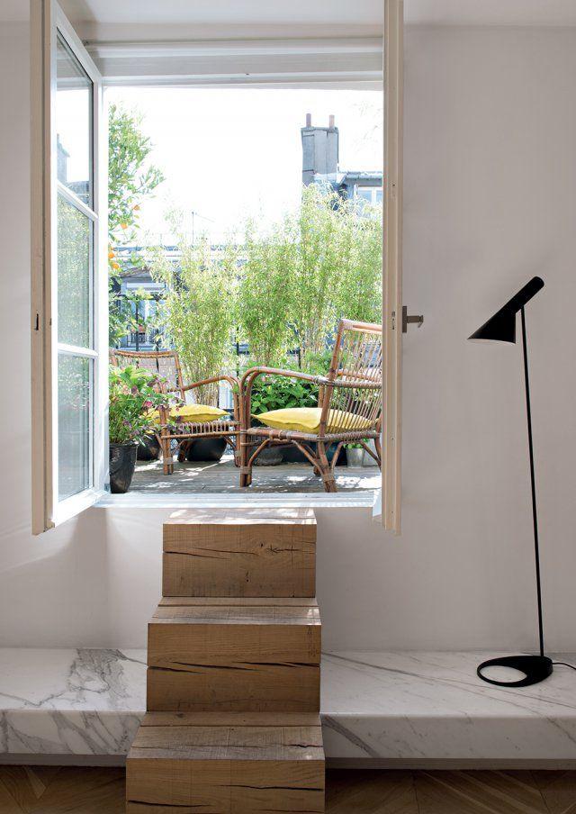 Perchée sur les toits, la terrasse est accessible par quelques marches. Dessinés par Jacques Leseur, ces trois billots en chêne brut se bougent à volonté. Fauteuils en rotin dénichés aux puces de Saint-Ouen. Lampadaire Arne Jacobsen chez Poulsen.