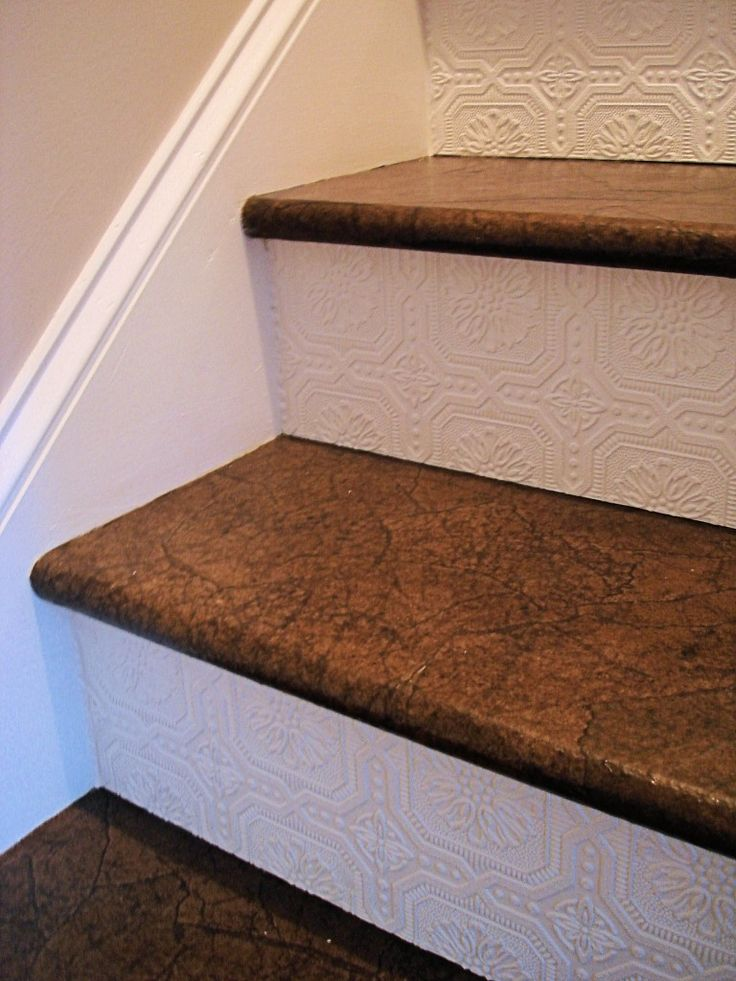 Paintable, textured pre-stick wallpaper applied to stair risers (which are done in the ripped brown paper technique.)