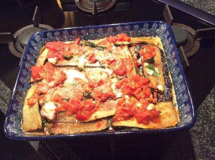 Aubergine en courgette, in lange plakken snijden, met zout het vocht eruit laten trekken. Deppen en in de olie even bakken. Tomaten saus zelf maken, 6 tomaten in blokjes in de olie braden met een uitje en twee teentjes knoflook. Dan laag voor laag opbouwen, met mozarella plakjes en geraspte pecorino kaas ertussen. 15 min. In een voorverwarmde oven van 175 gr. Alles is al gaar het gaat erom dat de kaas smelt,