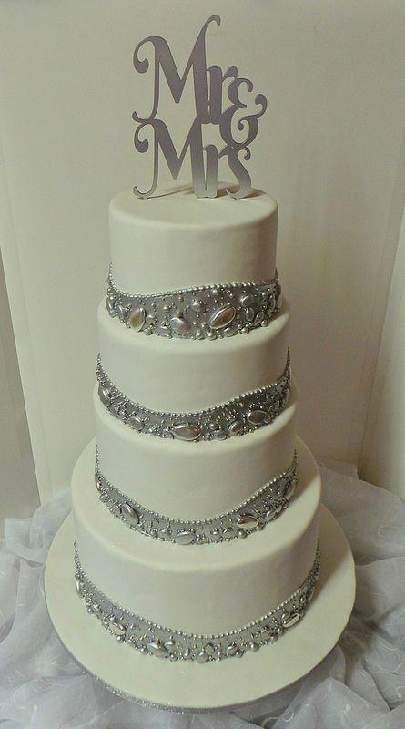 Four tier white & silver wedding cake