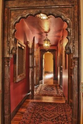 Antique moghul arches from India define the entrance to the hall and dining room. Antique wooden and metal screen jalis from India adorn the left wall. In the hallway are late 19th century Afshar rugs from southwest Persia.