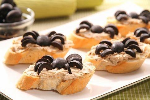Sardinky zbavte páteří, přidejte k nim nahrubo nasekanou šalotku, máslo, hořčici, sůl, pepř a vše důkladně rozmixujte. Rybičkovou pomazánkou pak potřete na kolečka pokrájenou bagetu. Zbývají už jen pavoučci! Olivy rozkrájejte podélně na půl a jejich část pak ještě znovu na menší obloučky. Ty pak budou tvořit tělo a pavoučí nohy.