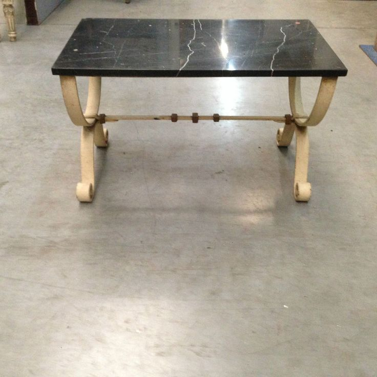 table basse en fonte de fer patinée années 40 piètement en X , dessus marbre noir veinée, bague en bronze . XX siècle.