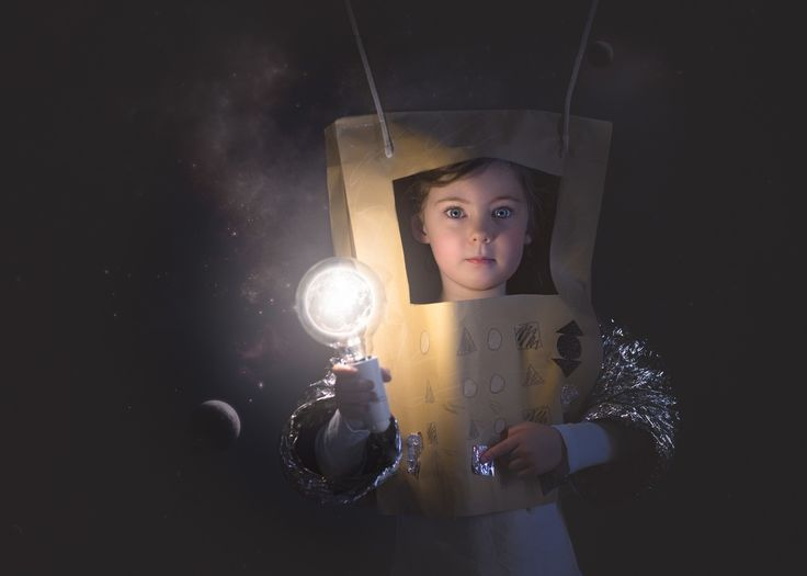 Composite photography of the moon in a lightbulb. Alien astronaut playing with the planets. Studio light. Diy costume for robot.
