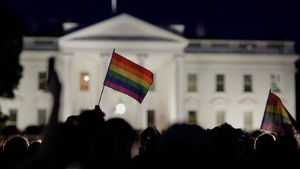 A rainbow flag is held up during a vigil after the worst mass shooting in U.S. history at a gay nightclub in Orlando, Florida, in front of the White House in Washington, U.S., June 12, 2016. REUTERS/Joshua Roberts     TPX IMAGES OF THE DAY