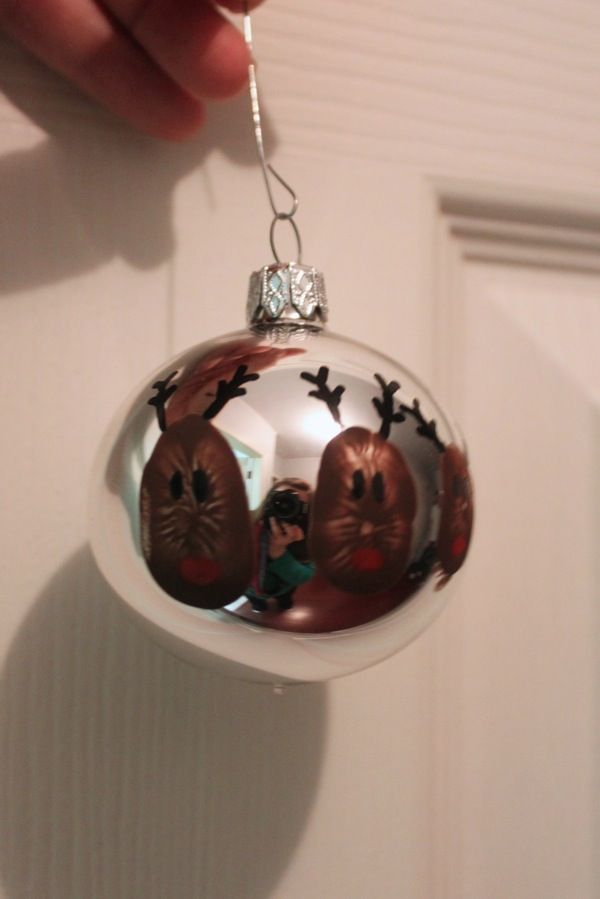 A glass bulb decorated with a family of thumbprint reindeer A Yearly Tradition: Handcrafted Christmas Ornaments - Mama. Papa. Bubba.Mama. Papa. Bubba.
