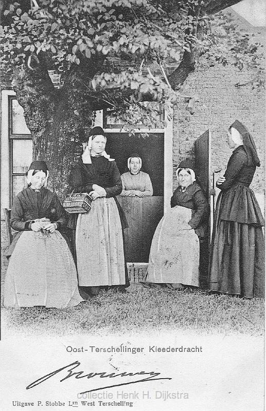 Oost-Terschelling. Vijf vrouwen in dracht poseren onder een boom bij een voordeur. Een vrouw leunt op de onderdeur. (1880-1908) #Terschelling