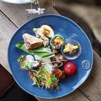 はじめにご紹介するのは『CASA DE CHA 1472(カサ デ チャ イチヨンナナニ)』さん。新義真言宗総本山の寺院・根来寺近くに店舗を構え、世界の料理を提供するおしゃれなカフェです。こちらは串焼き料理のサテや、アチャールと呼ばれる野菜のピクルスなど、色とりどりのインドネシア料理が並ぶワンプレートです。お料理はもちろん、器もとっても素敵ですね!