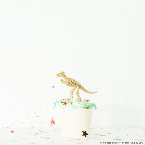 恐竜の日...  恐竜の日 JP  1923年の月17日 ローイチャップマンアンドルーズという アメリカの動物学者がゴビ砂漠に旅立った日です そこからの旅で恐竜の卵を世界ではじめて発見したとか  映画ジュラシックパークのシリーズ第一作で ラストシーンでティラノサウルスに 垂れ幕がワーって落ちてくる場面 あのかっこいいシーンをイメージして この写真を撮りました  恐竜の骨がのっかっているのはカップケーキです この恐竜はケーキのデコレーション用のもので 食べられません ちなみにまわりに散りばめたきらきらのスパンコールも 食べられませんというか食べちゃダメです笑 岡尾美代子