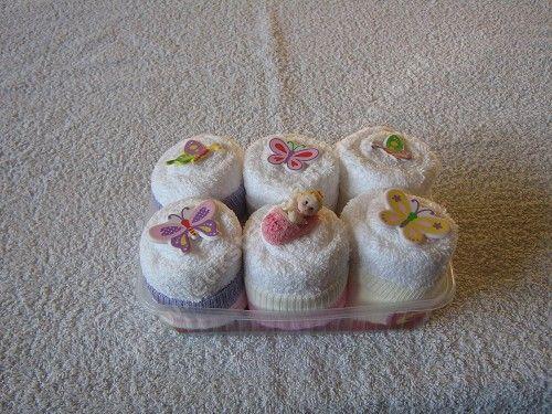 """6 Cupcakes.  2x monddoek, 2x slab, 2x romper, 3 paar sokjes 0-6M, 6 cupcake vormpjes, Parelknop speldjes, Bloemetjes, Cupcake topper baby, Baby zeepje, Lint. Cupcake doosje.  Werkwijze: Vouw de spuugdoekjes, slabbers en rompers op in 3e en rol deze op. Vouw een sokje om het rolletje, en sla de rand terug. bindt om het rolletje een lintje, zet het rolletje op een cupcake vormpje.  prik parel knopspelden in de """"cupcake"""" als deco. Versier het verder met de overige spullen. En zet ze in het…"""