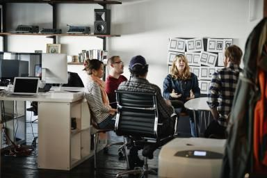 Businesswoman leading meeting in startup office - Thomas Barwick/ Stone/ Getty Images