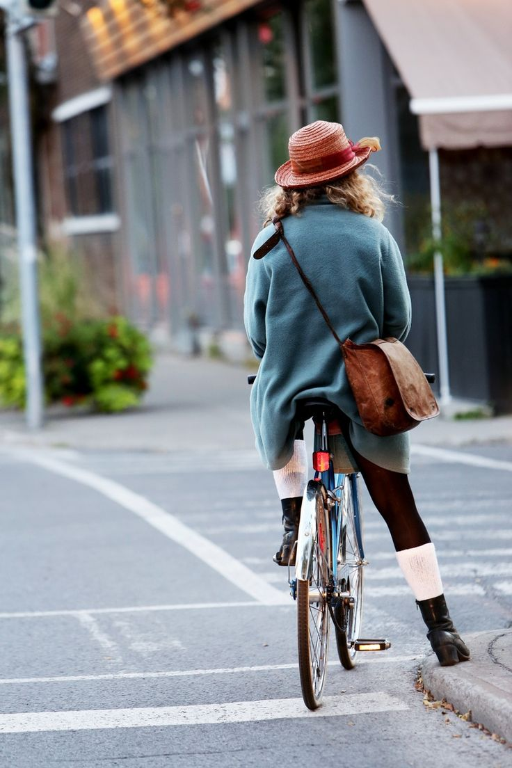Woman in Blue Coat Wearing Pink Straw Hat Riding Road Bicycle on Gray Concrete Street Road during Daytime