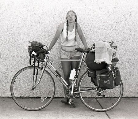 """Laura Orton, a hospital dietitian from Michigan, was riding a big loop out of Seattle, Washington, when she came our way. The date was July 23, 1982. Her portrait is notable in that it was the first one.  She liked the roller coaster rhythm of bicycle touring — the highs and lows that come every day on the road.We experienced 13 miles of tarred, bubblegum road, the temperature at 90 degrees, with man-eating flies."" Nonetheless she was looking forward to a tour in Europe."""