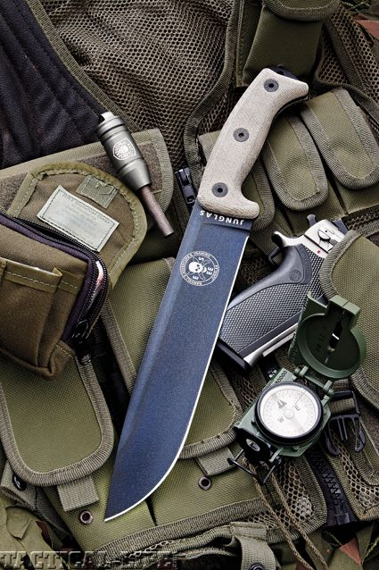 """ESEE has brought out a new knife that should appeal to the """"hard-use"""" knife enthusiast. The """"Junglas"""" (pronounced """"hoonglas"""") fixed blade is similar in size to the original RTAK and many will be quick to make comparisons. The overall length is 16-1/2 inches and sports a blade 10-3/8 inches long. The steel is 1095 with a black powder coating and Micarta handle scales. At its thickest point the blade is .188 inches and has a high saber grind. The extended pommel is flattened for hammering"""