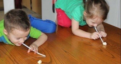 Make a bowl of popcorn and challenge your kids to play the Popcorn Olympics.