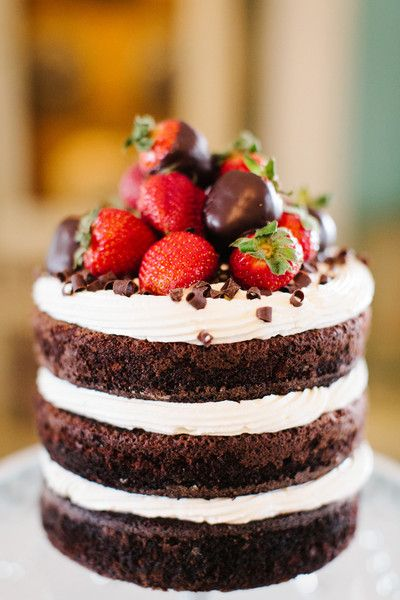 This unique cake idea has unfrosted sides giving it a deconstructed feel but the chocolate covered strawberries on top add a decadent touch! | Rustic Wedding Cakes {Riverland Studio}