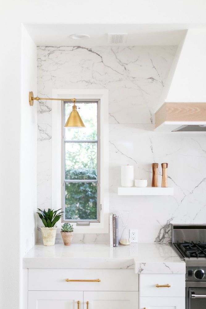 marble counter and backsplash featuring bright metallic accents