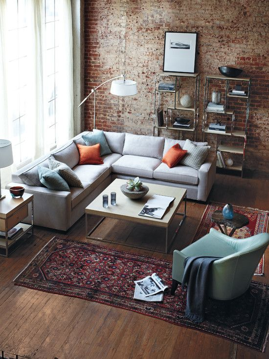 Rustic modern/industrial living room. Brick wall accent, L shaped grey sofa, wood coffee table and Persian rug.