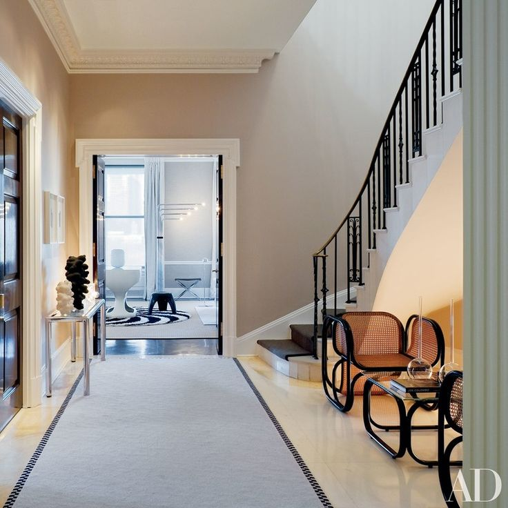 The entrance hall features a neutral color palette, and the staircase's brass railing inspired the home's graphic interior design | archdigest.com