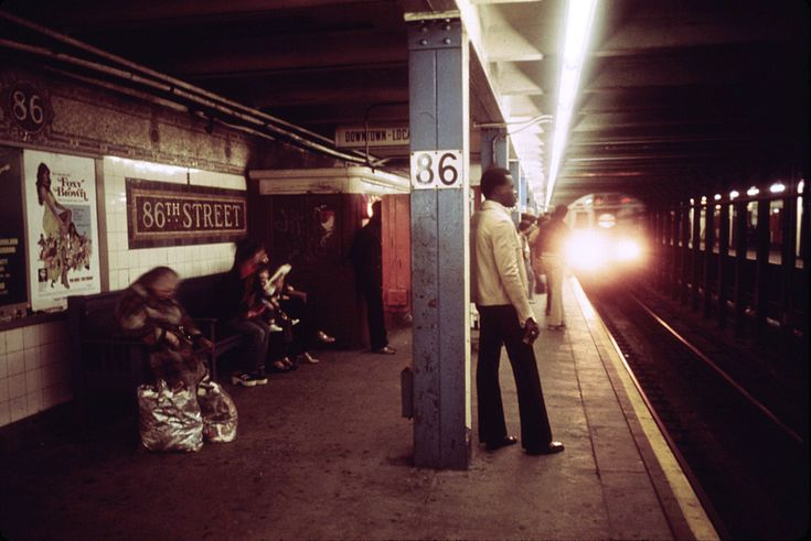 Passengers wait for a Lexington Avenue Line subway train on one of the platforms of the New York City Transit Authority, April, 1974. (Jim Pickerell/NARA)