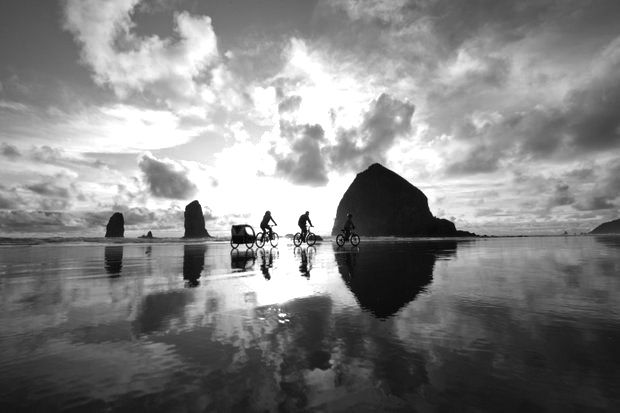A family riding #bikes at #Oregon's famed Cannon Beach