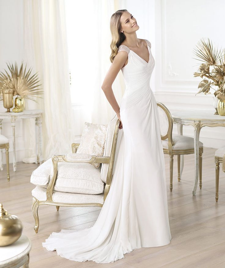 Draped wedding dress in gauze. V-neck with straps and semi sheer in tulle with pearl embroidery, flared skirt gathered at side.