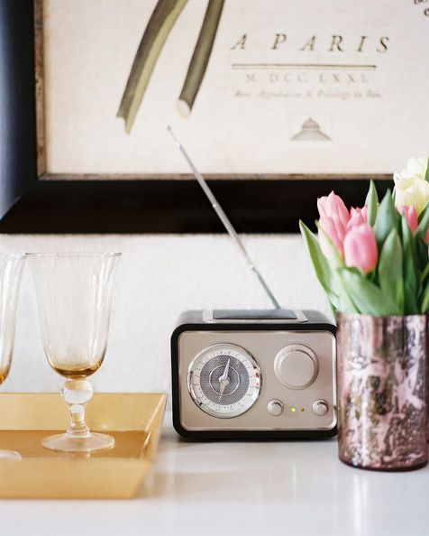 A small radio, a tray of glassware, and a vase of flowers on a white surface