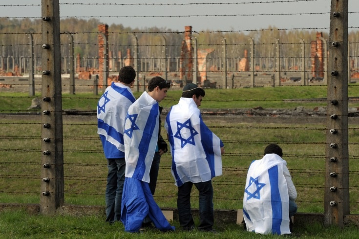 """Israeli youth wear their national flag at the Aushwitz death camp as part of the """"March of the Living"""""""