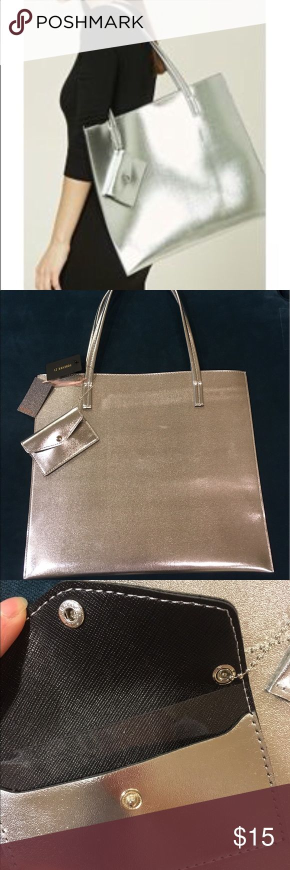 Forever 21 metallic silver tote bag+ coin pouch Look chic with this statement metallic silver tote bag by forever 21! Perfect for a day out to hold a lot of stuff! Comes with a cute coin pouch that has a divider, can hold a few cards! Tote measures: 15.5x13.75 inches ✅Bundles!✅❌no trades❌ Forever 21 Bags Totes