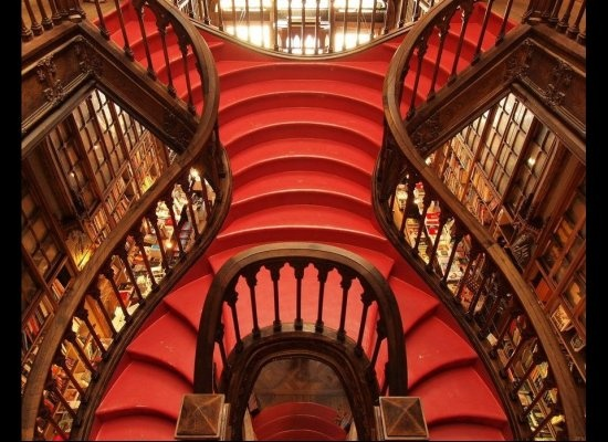 """""""Opened in 1906, Lello is one of the world's most beautiful bookstores, thanks largely to its centerpiece: this glossy red staircase with carved wooden banisters that leads up to a glass atrium"""" - Porto in Portugal"""