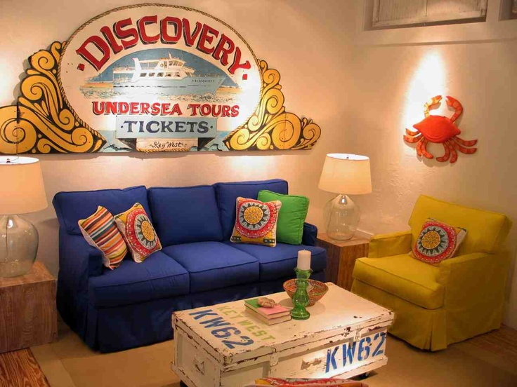 LIVING ROOM, BRIGHT SLIPCOVER FURNITURE. here we used a large sign from an old Key West boat tour company as artwork behind the sofa.  The coffee table was an old tool chest we painted in a fun nautical motif.