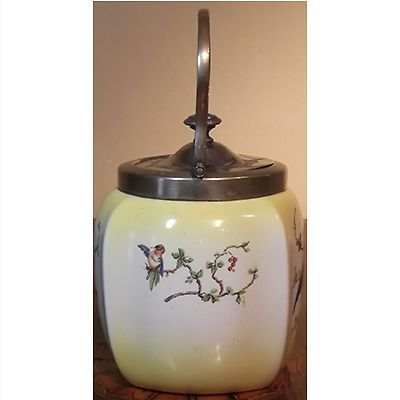"""Yellow ceramic biscuit barrel with a blue bird on the front. The lid and handle are silver plate. The front of the jar is marked; """"C.W.S EPNS"""" The C.W.S mark is for Co-Operative Wholesale Society, Manchester England, founded in 1863 it produced C.W.S Brand goods for the Co-Operative Societies throughout the UK including: food, furniture, clothing, and household products. In 2001 the name was changed to The Co-Operative Group. The """"Made in England"""" stamp on the base dates it to the 20th…"""