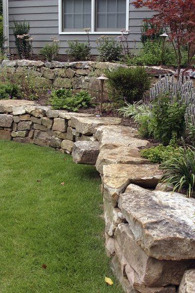 a hand laid retaining wall made out of natural stone two terraces are filled with low maintenance landscaping the terraces smooth out angle between the
