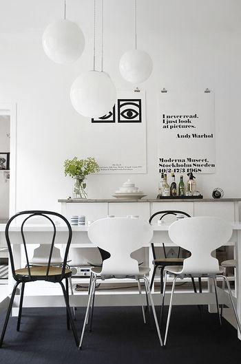 """画像のポスターの文字列やデザイン、椅子のフレーム。沢山の""""黒""""の情報がこの空間内にはありますが、落ち着いて見えるのは、床に敷いたカーペットの""""黒""""がきいているから。  白いインテリアを目指すあまり、床まで""""白""""にこだわるのは得策ではありません。白を印象づけるには、白を引き立てる色も必要です。  床一面を白色やオフホワイトにすると、材質によっては目に眩しく落ち着きません。白は膨張色でもあるので、床がせり上がり天井も低く感じてしまいます。ラグなどで床の色を抑えると、白い壁面や家具がよく映えます。"""
