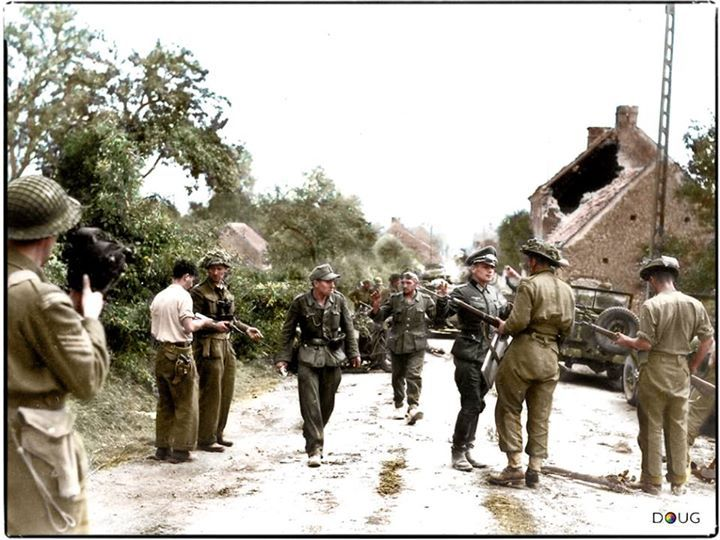Major David V. Currie (left with hand gun) of the 29th Canadian Armoured Reconnaissance Regt. (The South Alberta Regiment), is in conversation with R. Lowe of 'C' Company, at the time that members of 2.Pz.Div., commanded by Hauptmann Siegfried Rauch are surrendering to Sgt.Major G. Mitchell in Saint-Lambert-sur-Dives, Calvados.  Library and Archives Canada, pa-111565) (Colourised by Doug)