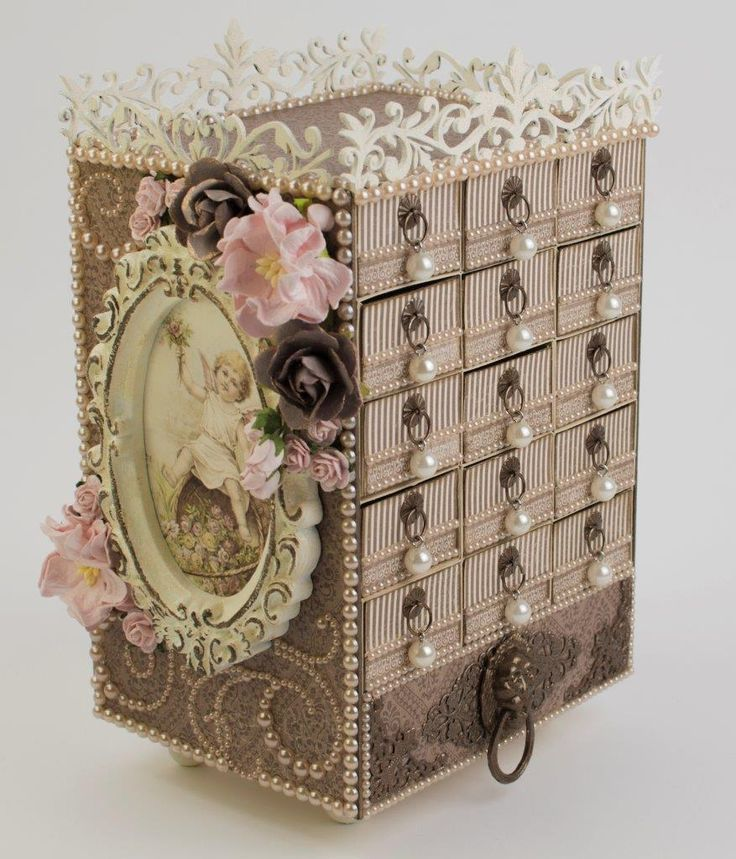 """Taras Studio_Box - This project is a little time-consuming. The little matchbox drawers can be stuffed with fun things like costume jewelry and candy.  This one is decorated with Pion Design's """"A Day in May"""" collection.  The frame was originally a turquoise color so it got several coats of ivory paint and then was accented with brown paint.  You can find this project on the Pion Design Blog here.  The little matchbox cutting file came from the Pazzles library here."""